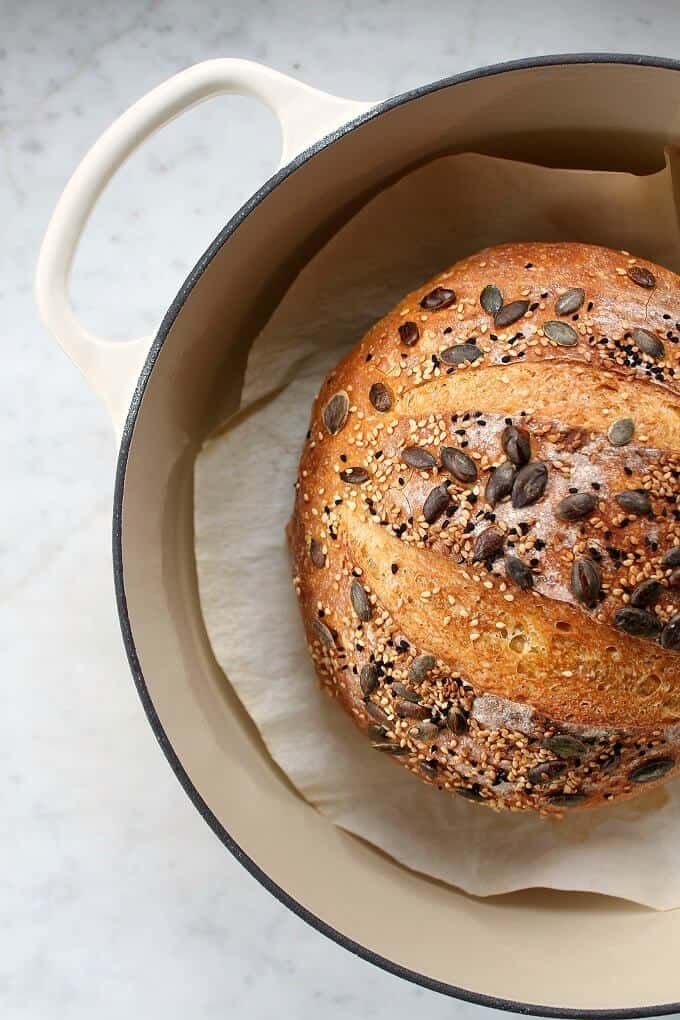 Pumpkin No Knead Bread - Bread boule topped with various seeds siting in an off white Dutch oven.