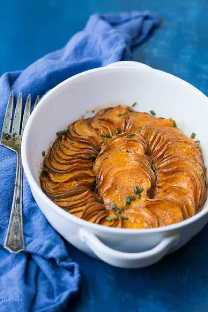 Scalloped sweet potatoes in a white oval dish on a blue table cloth and serving fork