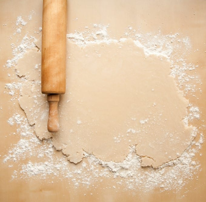Pie dough on a floured surface with a rolling pin