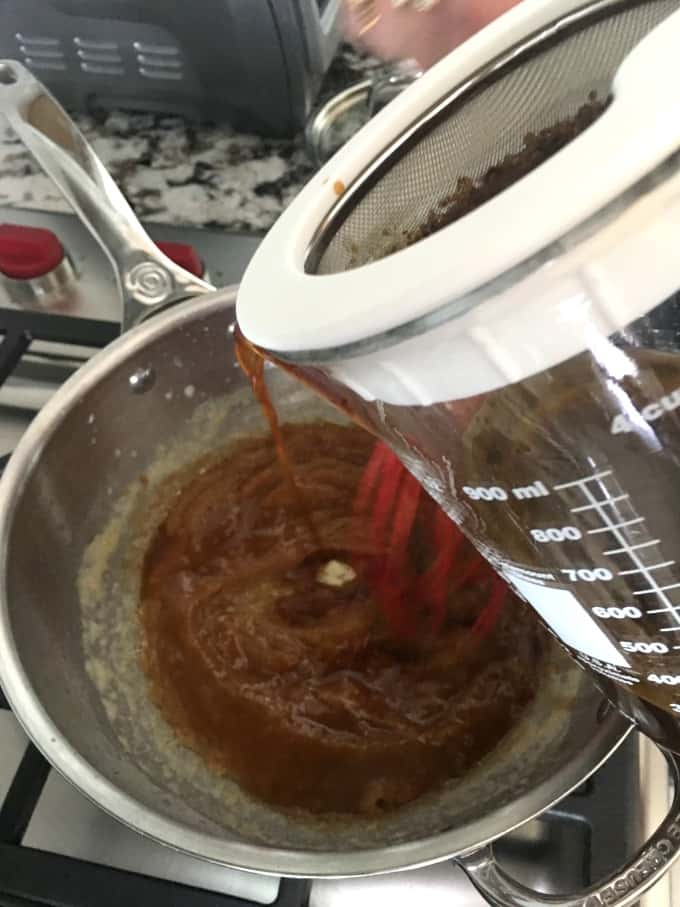 Whisking the drippings into a saucepan with roux
