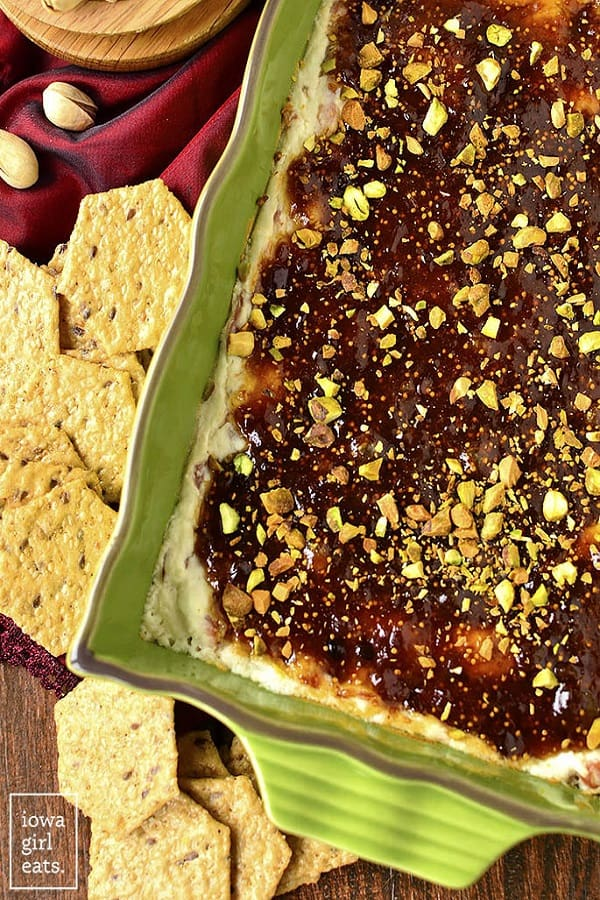Warm Fig and Prosciutto Goat Cheese Dip in a green dish with crackers