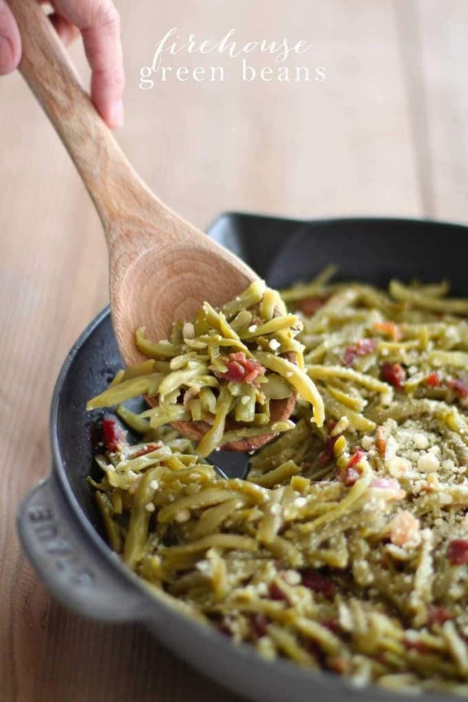 Green beans with bacon in a cast iron pan with a wooden spoon