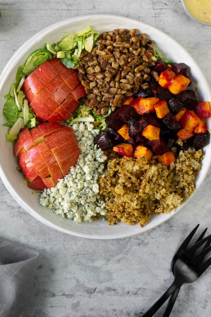 apples, blue cheese, brussels sprout, beets, and quinoa in a white bowl