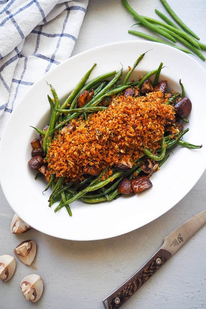 Roasted green bean and mushrooms with herbed breadcrumbs on a white serving plate