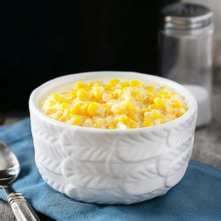 Slow Cooker Creamed Corn. Bowl of creamed corn sitting in front of slow cooker
