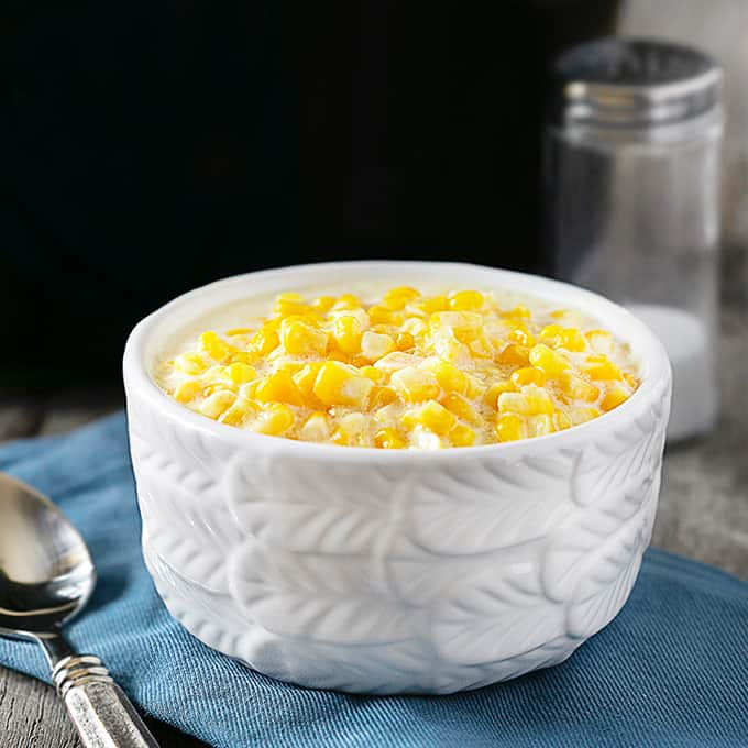 Bowl of Creamed Corn with crockpot in the background.