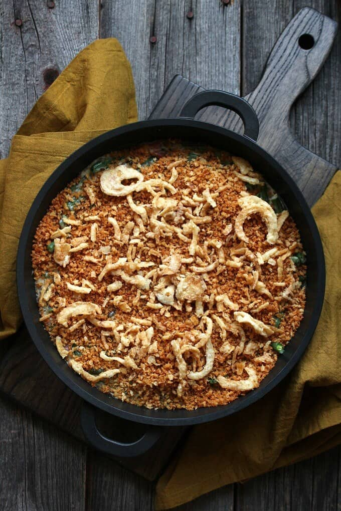 Zesty Green Bean Casserole - An overhead shot of a golden crumb and onion topped casserole in a black baking dish surrounded by yellow napkins on a grey wooden background.