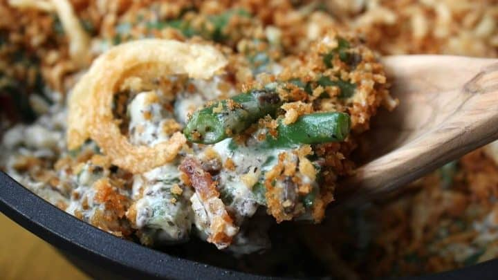 Zesty Green Bean Casserole - Close up of a wooden spoon holding a serving of fried onion, bacon, and green bean casserole.