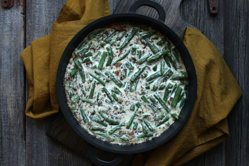 An overhead shot of a bubbling green bean casserole in a black baking dish.