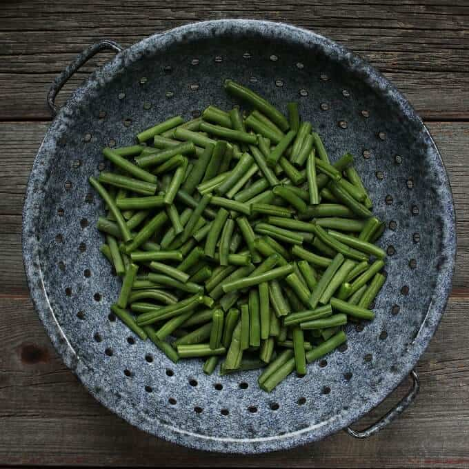 Bright green beans sit in a old fashioned grey colander.