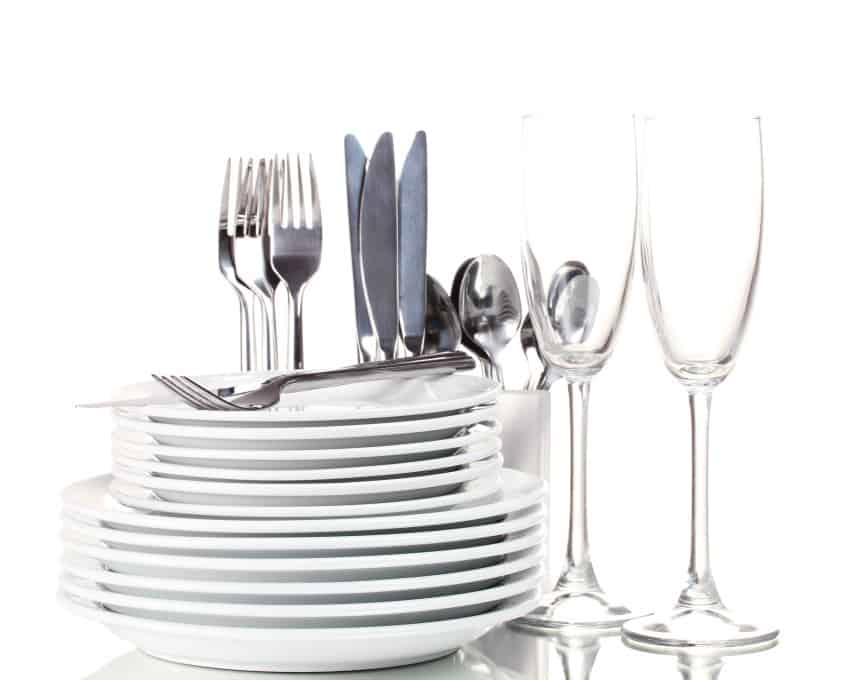 Stacked white plates and cutlery
