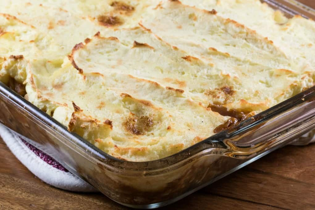 Casserole with a mashed potato topping in a glass baking dish