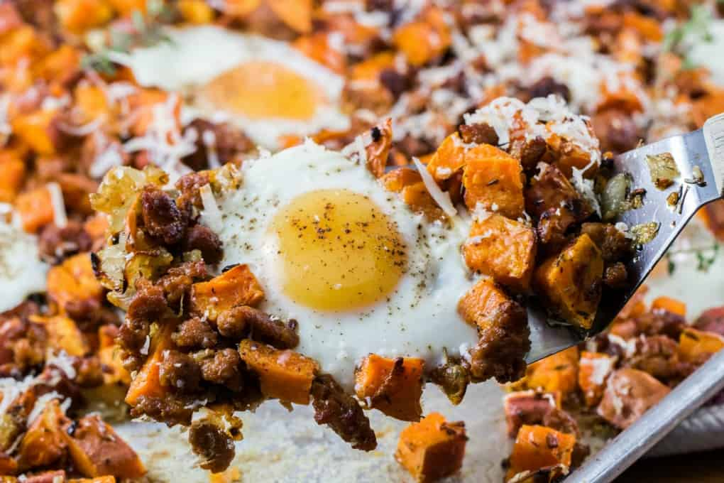 Sweet Potato Hash with Eggs and Sausage on a spatula taken from a sheet pan