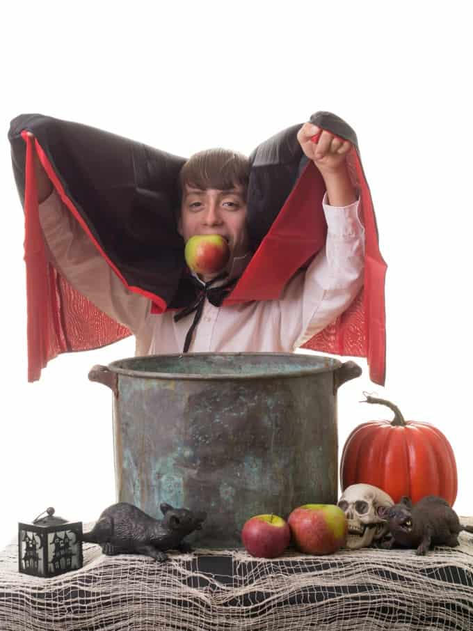 Boy dressed as Dracula bobbing for apples