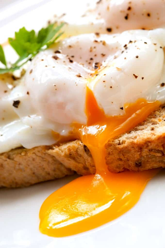 A perfectly poached egg on toast oozing onto a white plate.