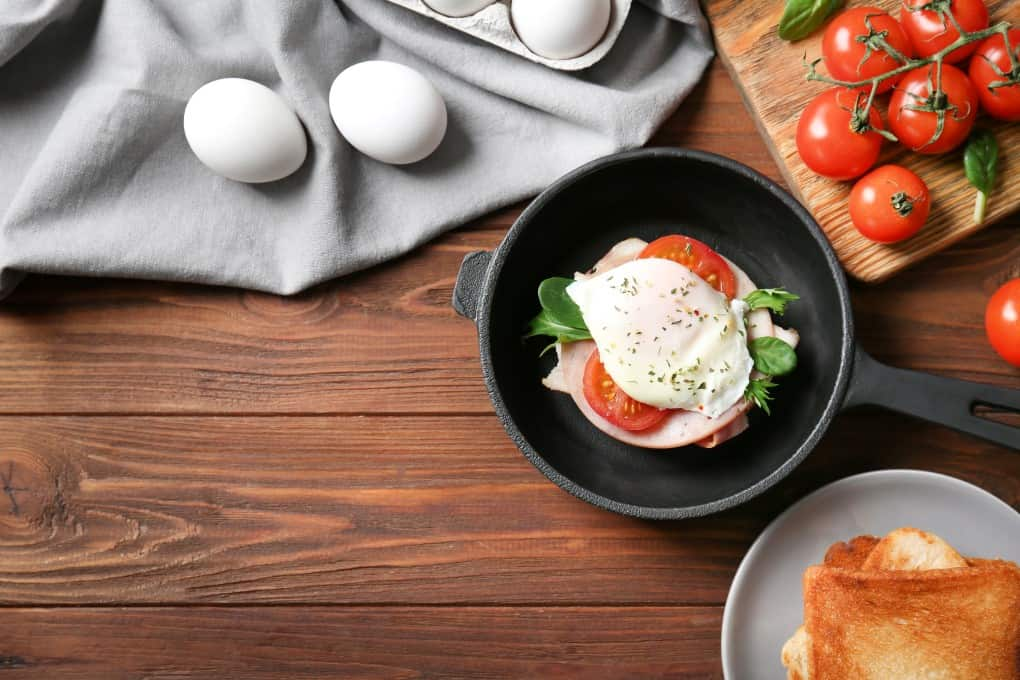 Eggs Benedict in a small cast iron pan with fresh eggs tomatoes and toast surrounding it.