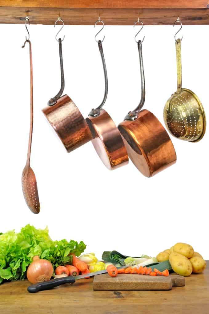 Copper pans and ladles hanging about vegetables on a cutting board.