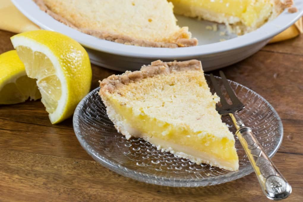Lemon Chess Pie on a glass dish with a fork and the pie in the background