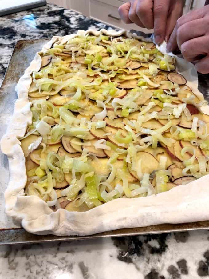 Folding up the edges of a potato galette with leeks on top