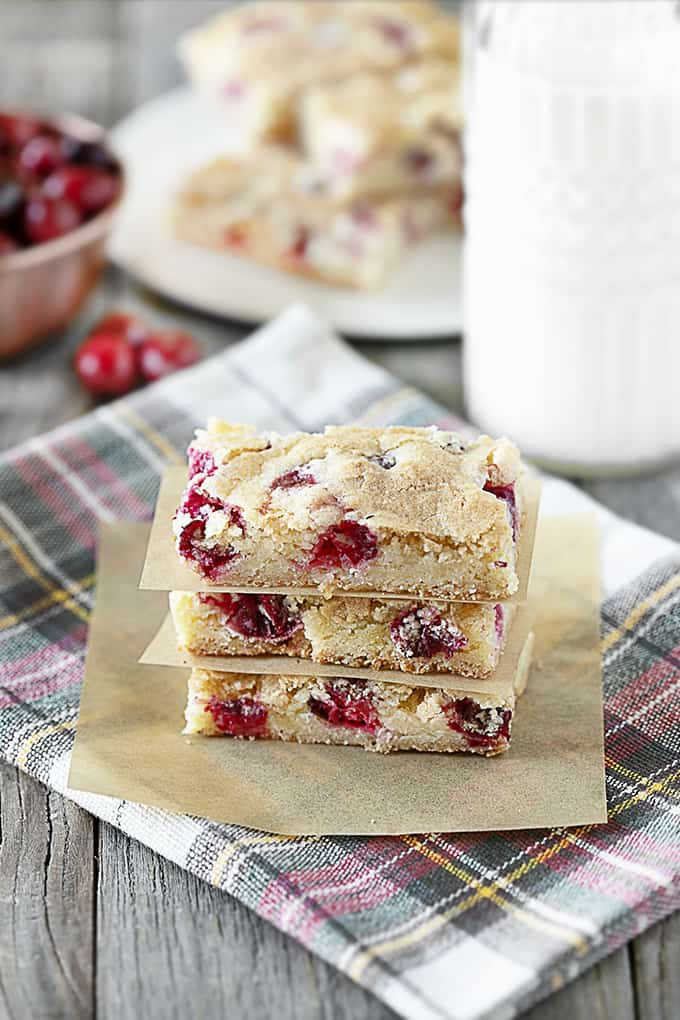 Cranberry bars stacked with parchment paper between on a plaid tea towel