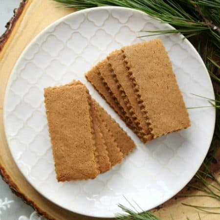 Speculoos Cookies (Classic Recipe)-A white textured plate filled with sparkling brown rectangular cookies surrounded by evergeen branches.