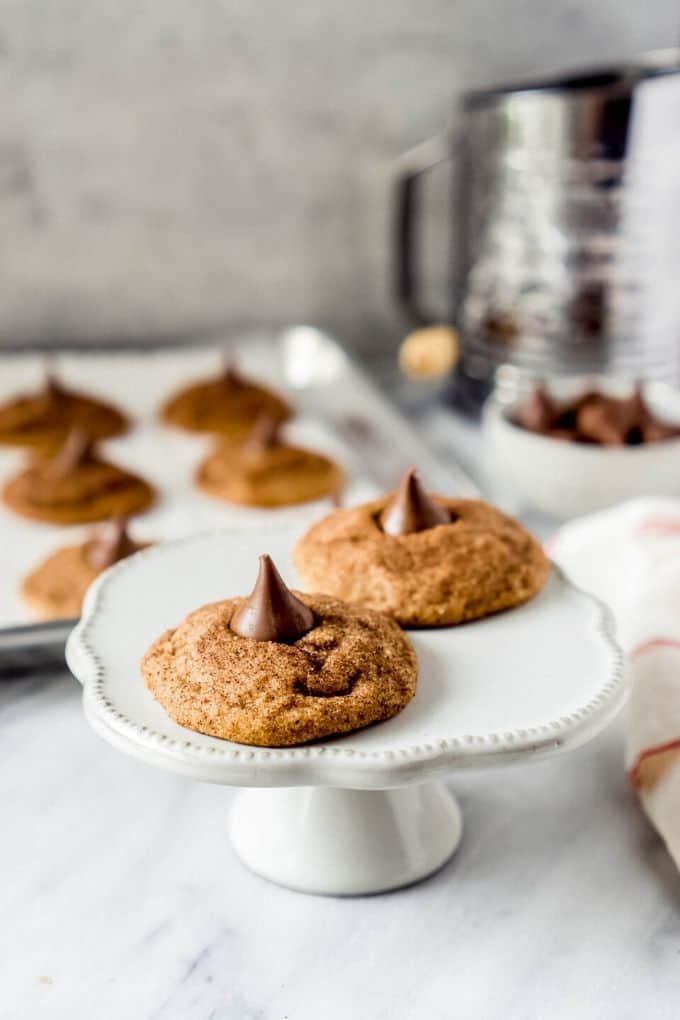 two snickerdoodle Hershey kiss cookies on a white cake stand with a flour sifter in the background