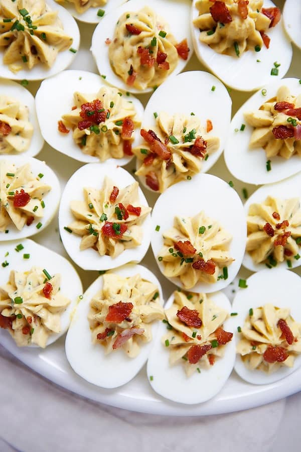 Deviled eggs with bacon and chives on a white serving plate