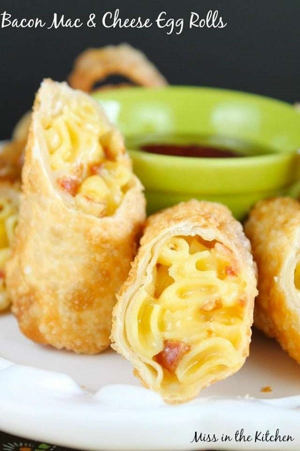 Bacon Mac & Cheese egg rolls in a white plate with a dipping sauce in a green bowl
