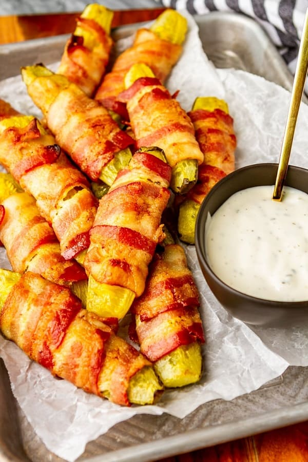Bacon wrapped pickles with a dipping sauce on a serving tray