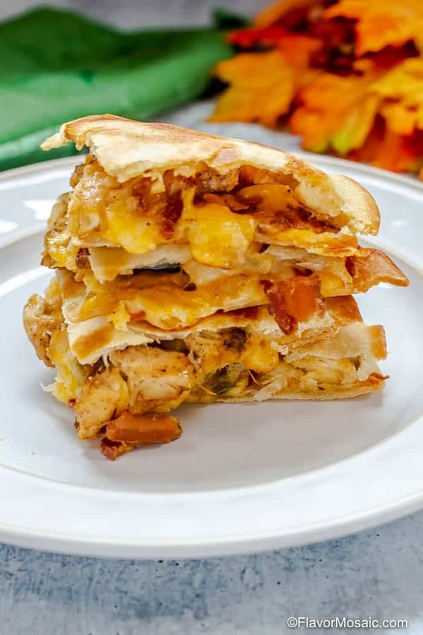 Chicken Bacon quesadilla pieces stacked on a white plate