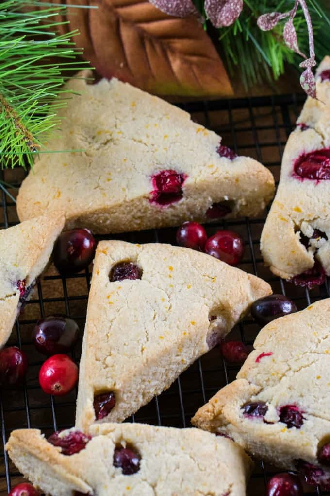 Overhead shot of scones on a black wire rack with fresh cranberries