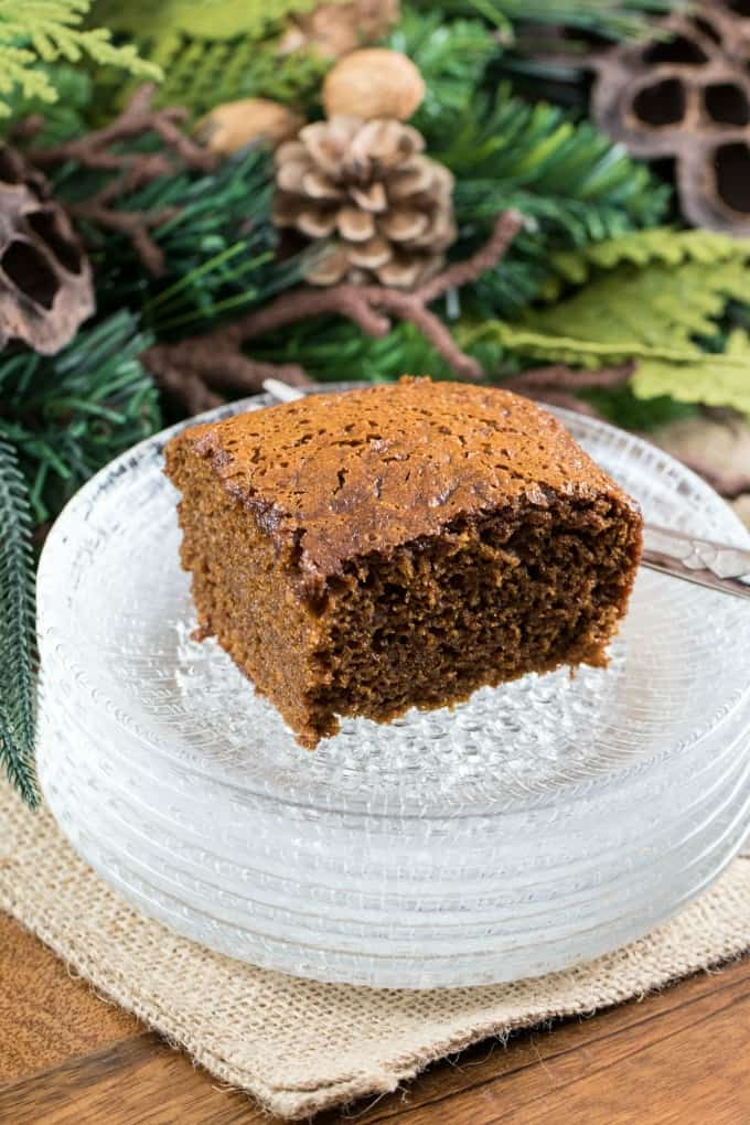 Gingerbread cake on clear glass stack of plates with greenery in the background