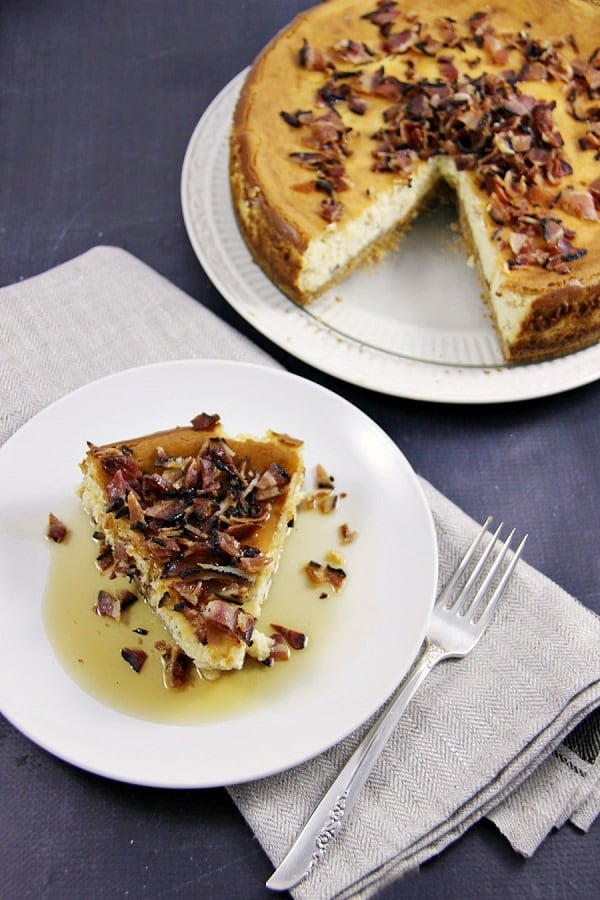 Maple bacon cheesecake with a slice cut on a small white plate with a fork