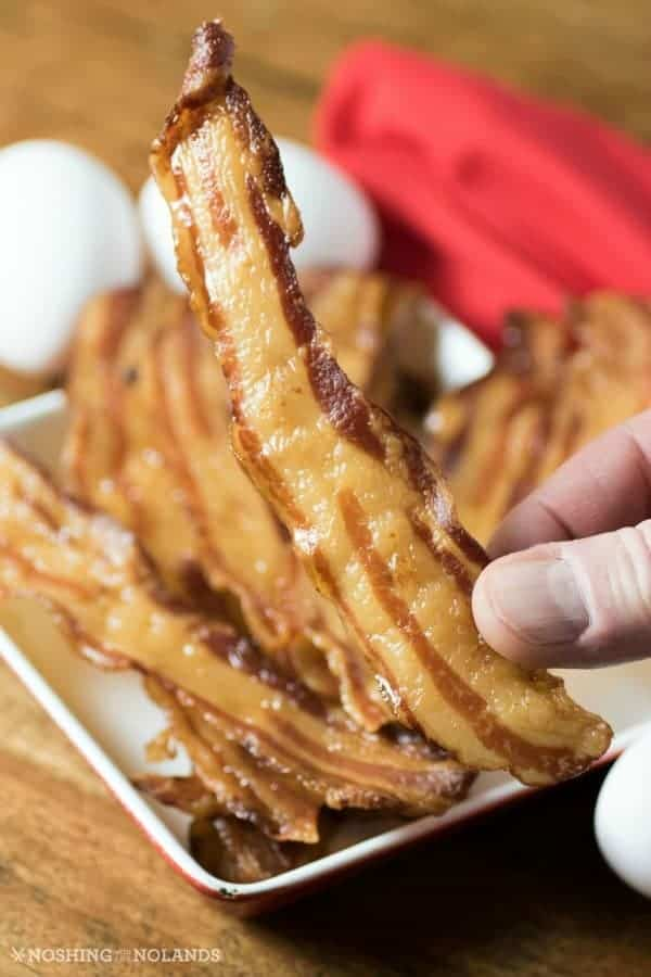 white plate of crispy bacon with one strip being held up