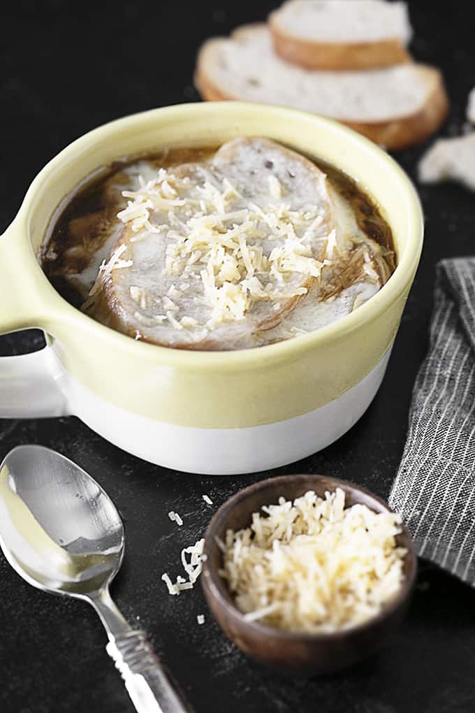 French onion soup in a bowl with a spoon and small bowl of Parmesan cheese