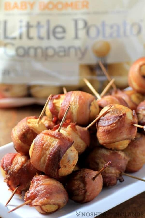 Little potatoes wrapped in bacon in a white plate