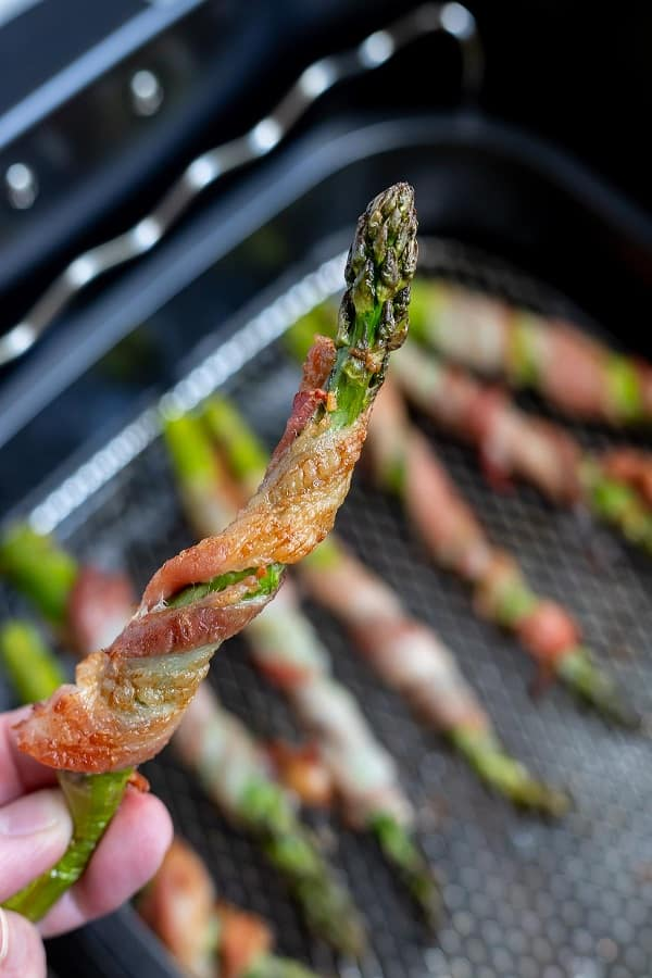 person holding an asparagus spear wrapped in bacon