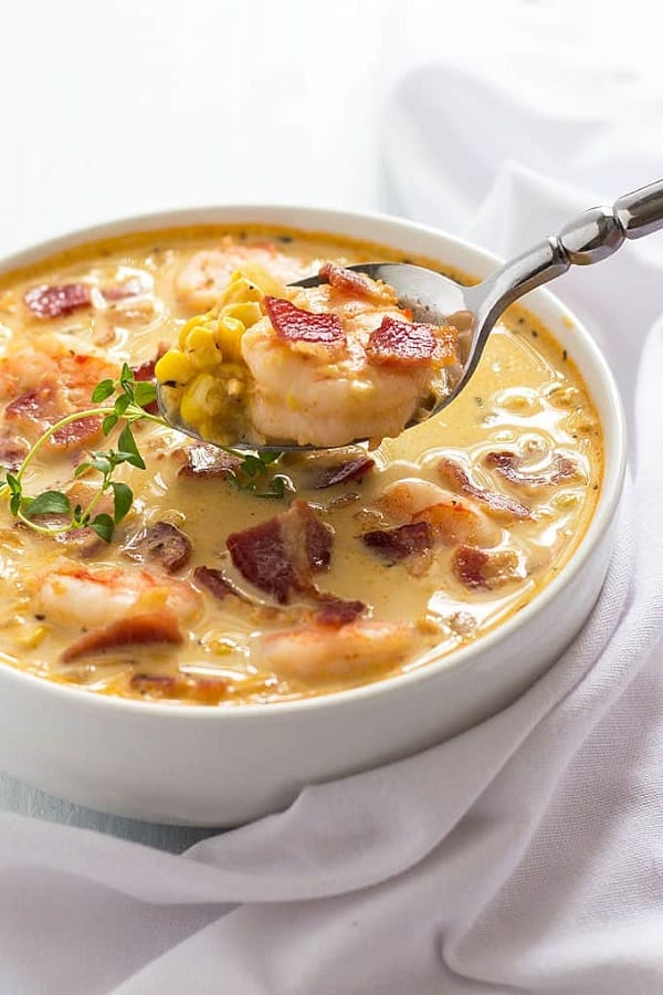 Bacon Shrimp and corn chowder in a white soup bowl with a spoon