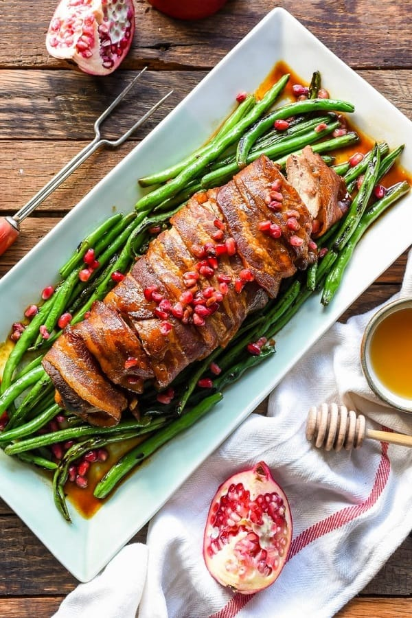 Bacon wrapped pork tenderloin on a white platter with green beans and pomegranate seeds on top