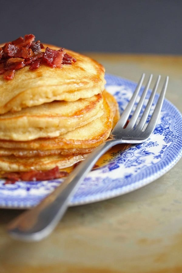 Stack of pancakes with maple bacon butter in a colorful plate with a fork