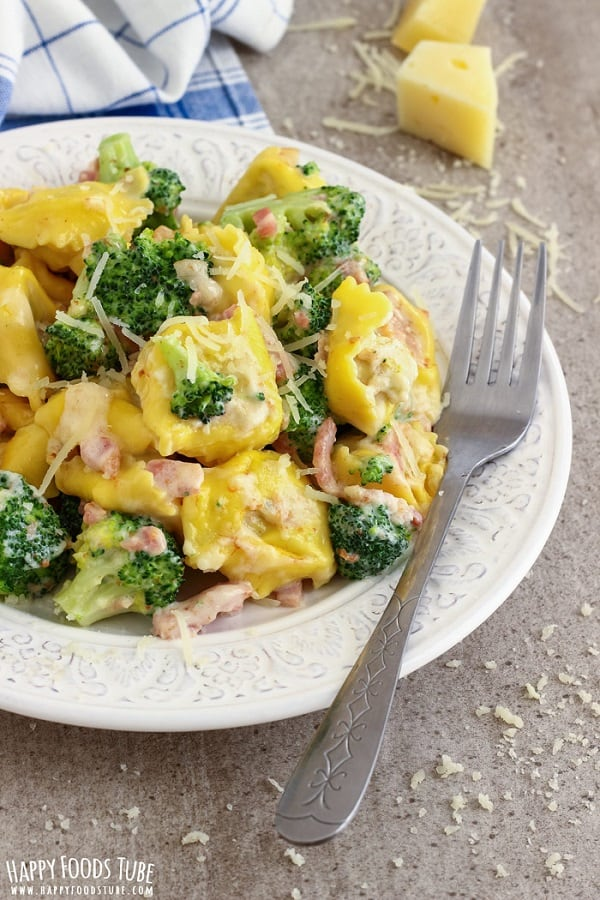 Tortellini pasta with broccoli and bacon in a white dish with a fork
