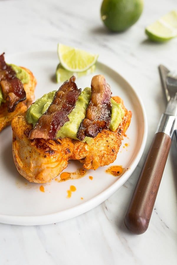 Bacon Chicken with guacamole on a white plate with lime slices