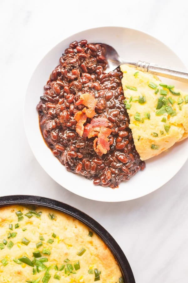 brown sugar baked beans with bacon on a white plate with corn bread and a spoon
