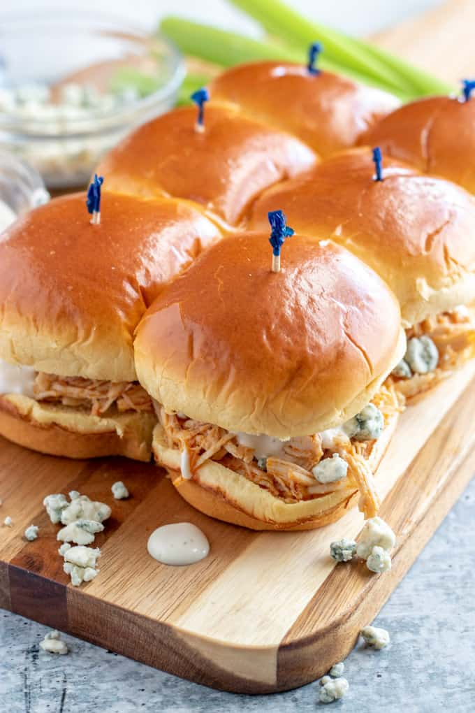 buffalo chicken sliders with blue cheese and ranch on a woodent board