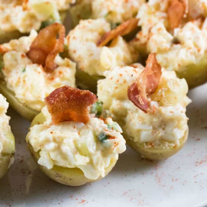 Close up of stuffed potatoes with egg salad and bacon