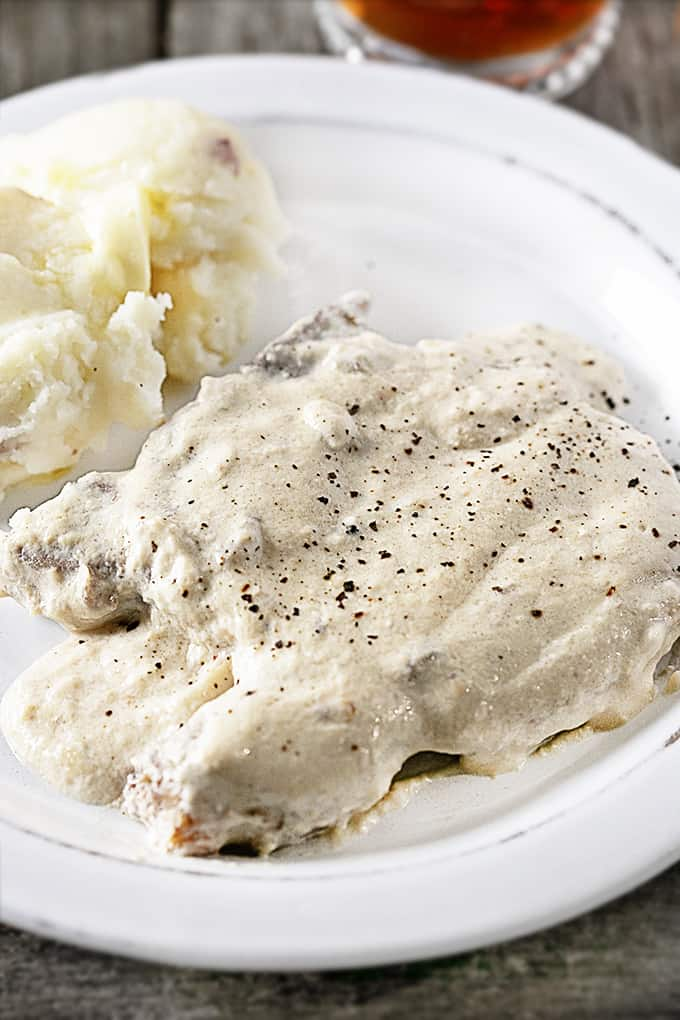 Slow Cooker Pork Chops on a white plate with mashed potatoes