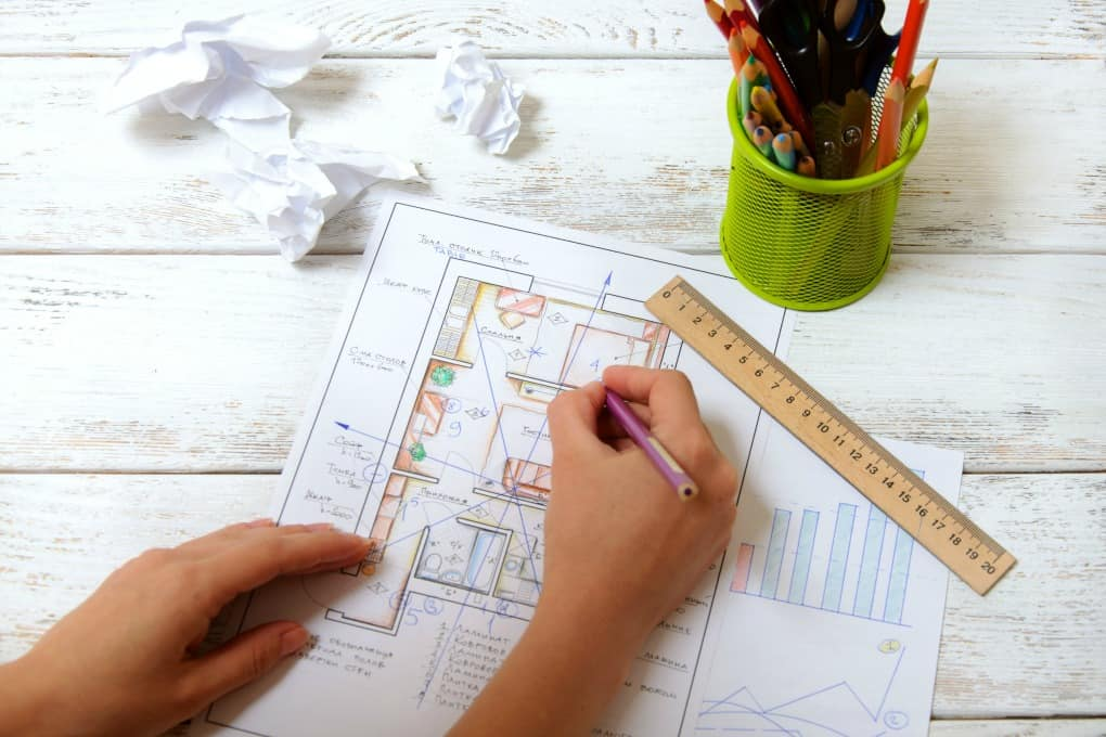 The woman draws a diagram of Feng Shui in the apartment layout. View from the top.