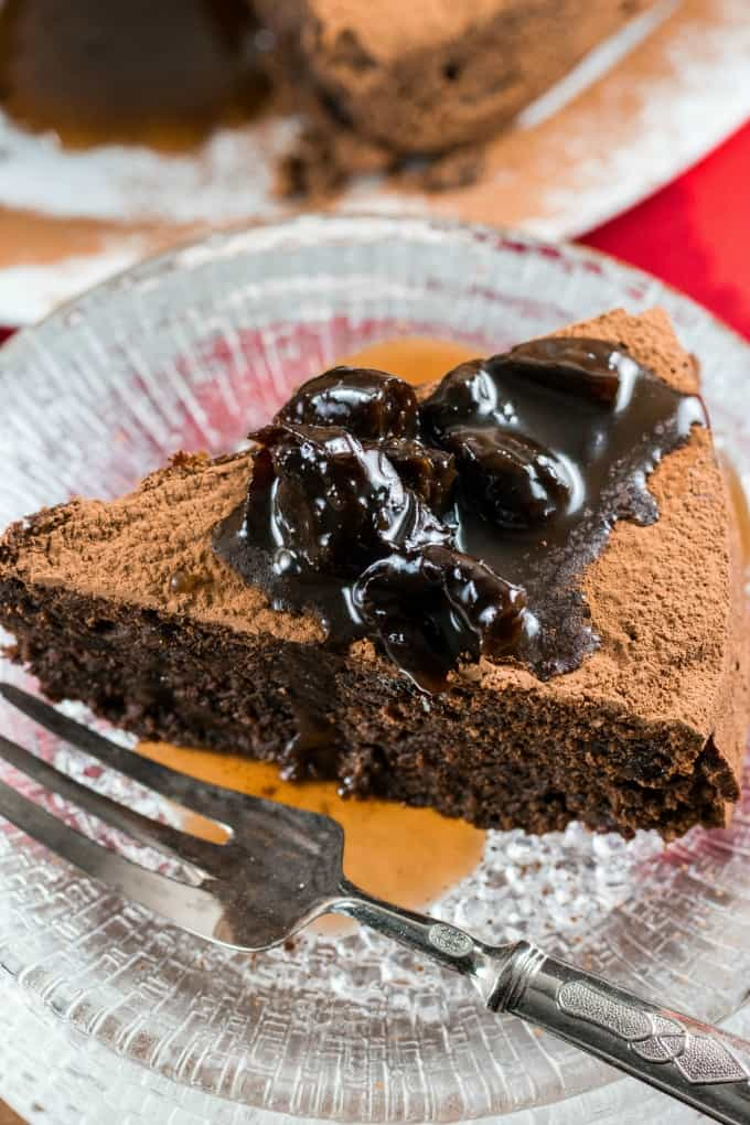 Fudgy Prune Chocolate Cake on a glass plate with a fork.
