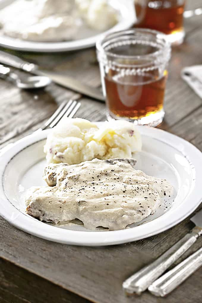Table setting with Slow Cooker Pork Chops on a white plate with mashed potatoes
