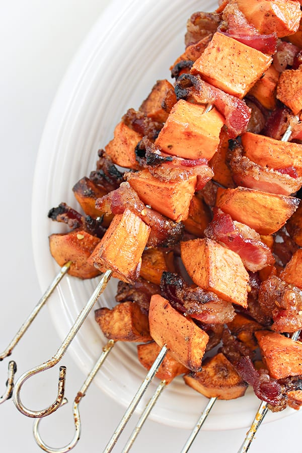 Sweet potato and bacon skewers piled on a white serving plate
